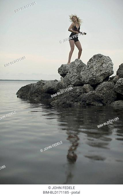 Caucasian woman standing on rocks by remote lake