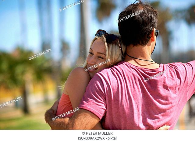 Couple outdoors, hugging, smiling, rear view