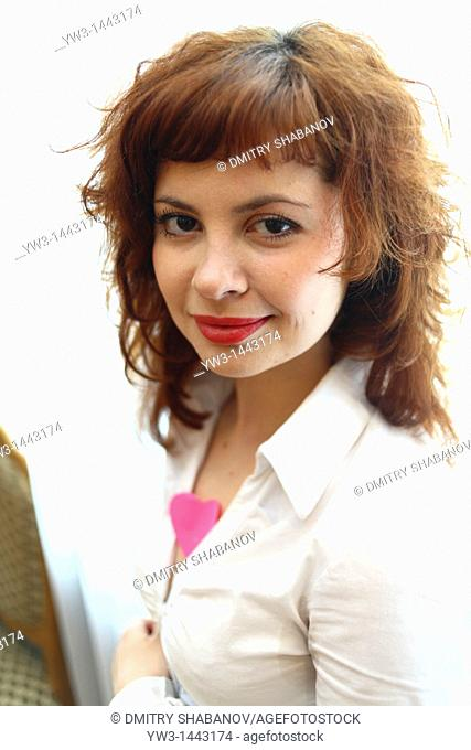 Pretty redhead young woman portrait with heart indoors