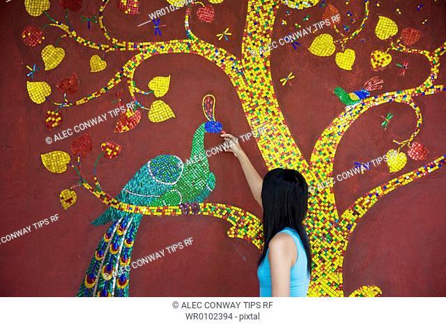 Chiang Mai, Thailand,Dhevi Mandarin Oriental resort. Woman looking at mural