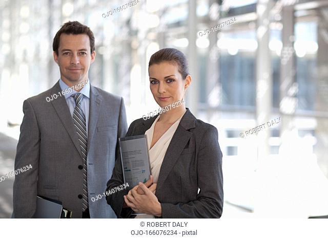 Portrait of smiling businessman and businesswoman in corridor