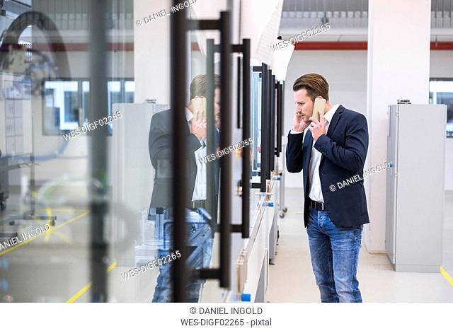 Man in factory shop floor on the phone