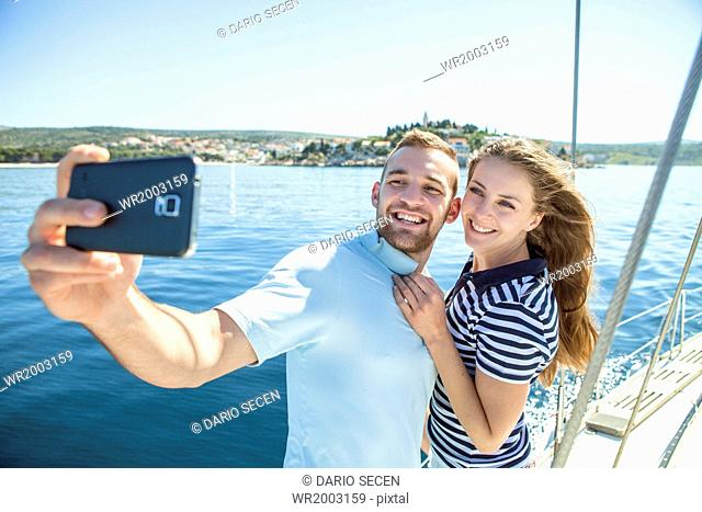 Couple photographing themselves on sailboat, Adriatic Sea