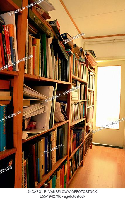 Hallway with very full bookcase. Door at the end of the hallway. There is also a version of this image with a surface blur applied to the image