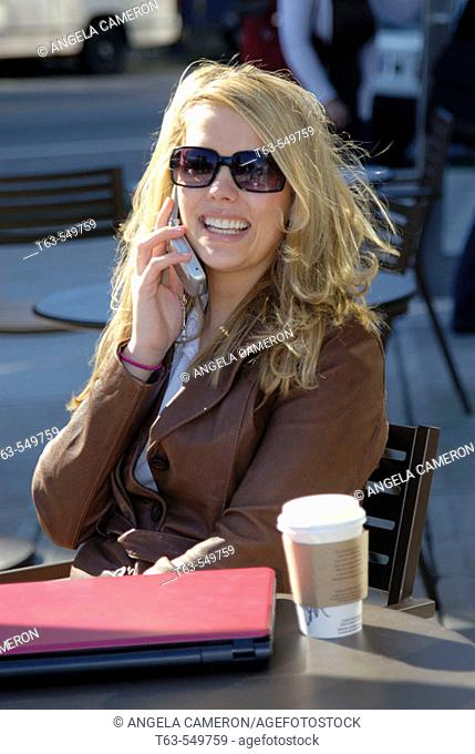 girl/woman 20 yrs on cell phone at cafe/coffee shop with coffee and laptop computer, sunglasses, city, urban, metropolitan, smiling, happy, street, traffic