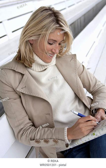 Blond woman doing crossword puzzle