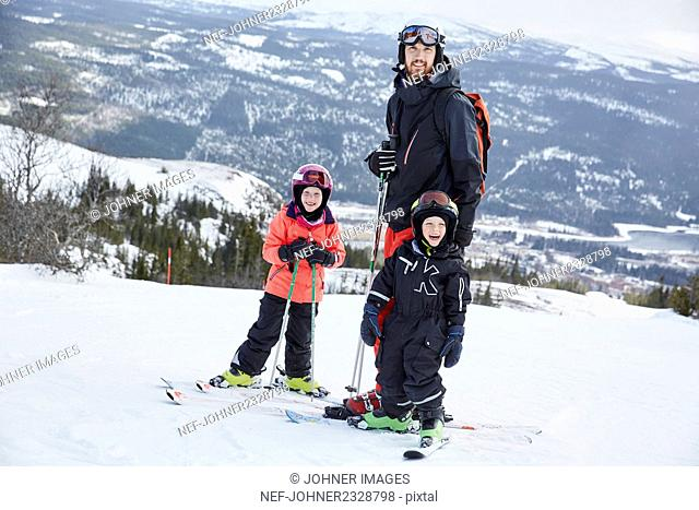 Father and sons skiing