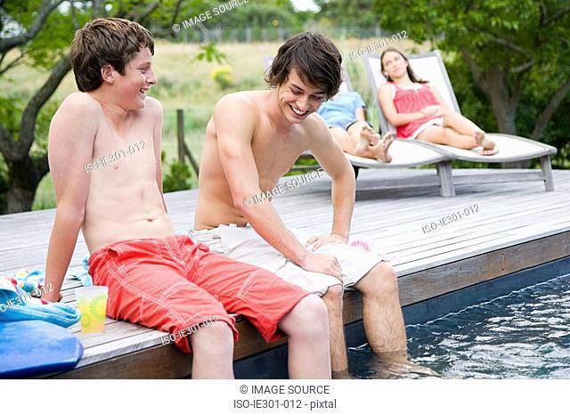 Teenage boys sat on the edge of a swimming pool