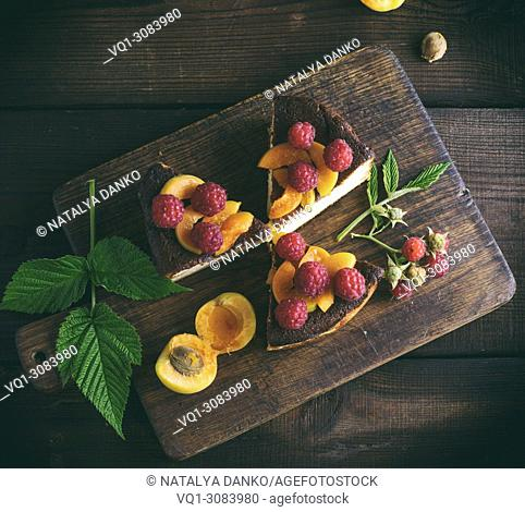 pieces of cottage cheese pie with strawberries and apricots on a brown wooden board, top view