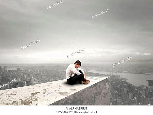 Alone desperate businessman sits on a roof. solitude and failure concept