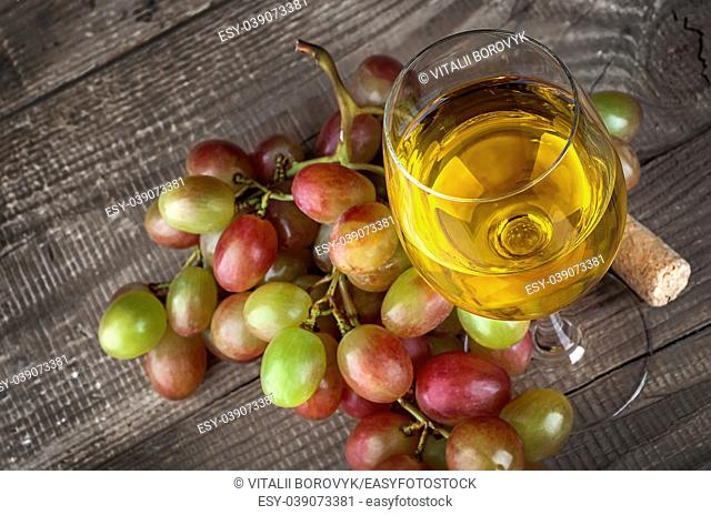 Glass of white wine with a cluster of grapes on wooden table background, top view