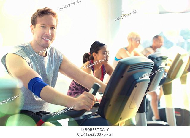 Portrait smiling man riding exercise bike at gym