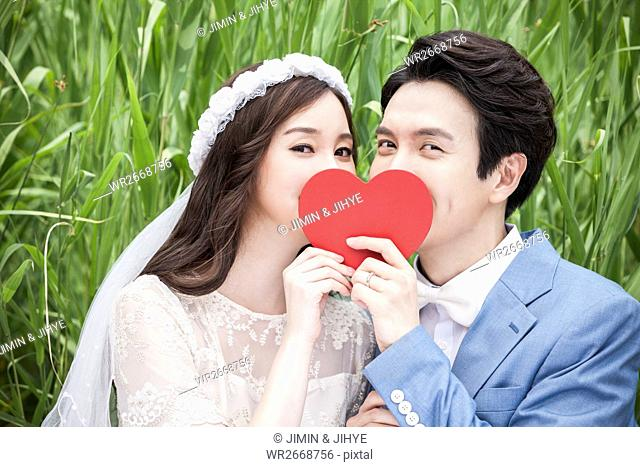 Portrait of young romantic couple with heart against green grass
