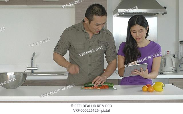 MS Young couple in kitchen standing and preparing food