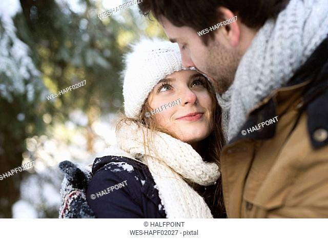 Portrait of hHappy young woman face to face with her partner in winter
