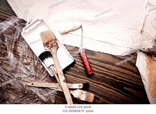 Still life of paint brushes and paint roller, overhead view