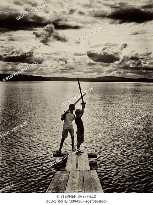 Two Boys with Wood Swords on Dock by Lake