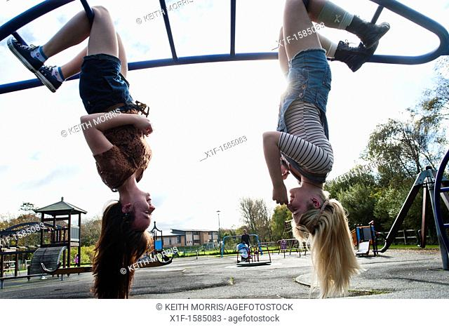 Two 16 17 year old teenage girls, hanging upside down in a playground, UK
