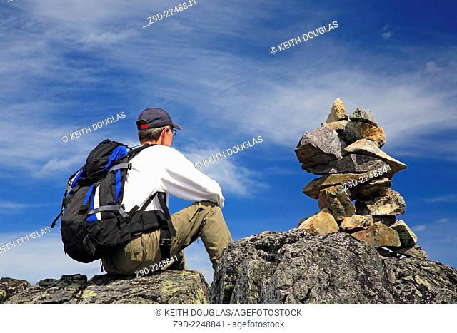 Hiker and rock cairn on trail, Hudson Bay Mountain, Smithers, British Columbia