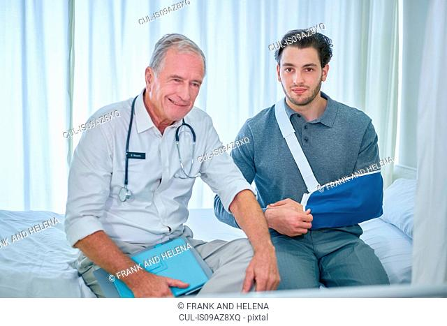 Doctor and man with arm in sling sitting on hospital bed