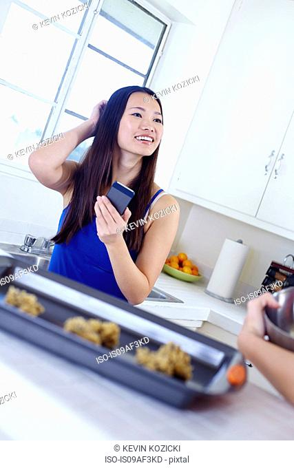 Young female friends in kitchen preparing food