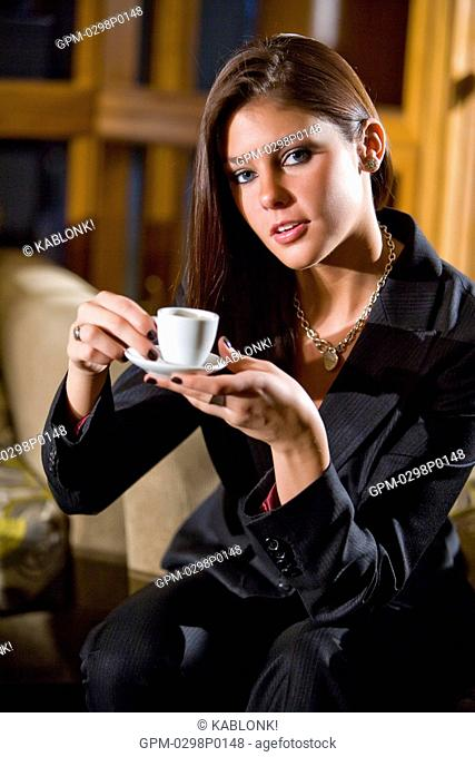 Portrait of confident young businesswoman sitting in modern hotel