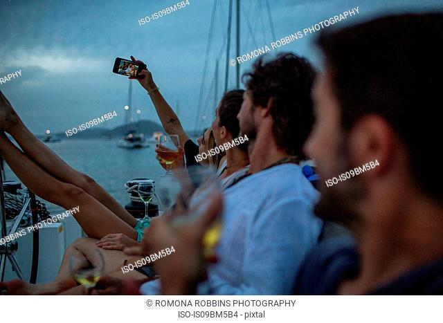 Four friends sitting on boat at dusk, drinking wine, taking selfie, British Virgin Islands