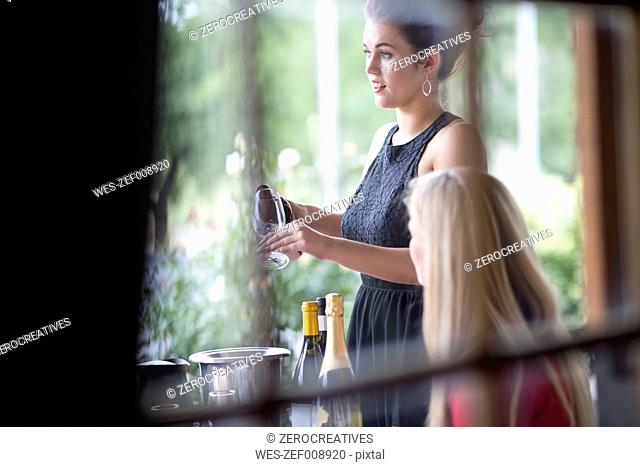 Waitress in restaurant serving red wine