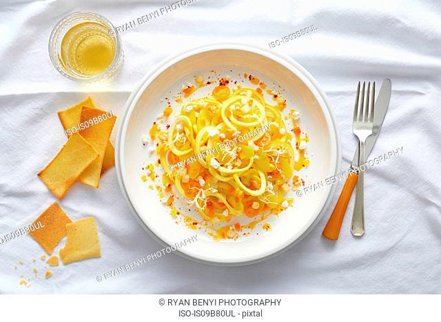 Spiralized yellow squash pasta with yellow cherry tomato, feta, orange pepper and a orange pepper coulis