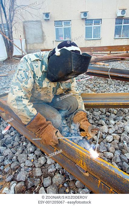 Welder in protective mask welding metal construction on open air