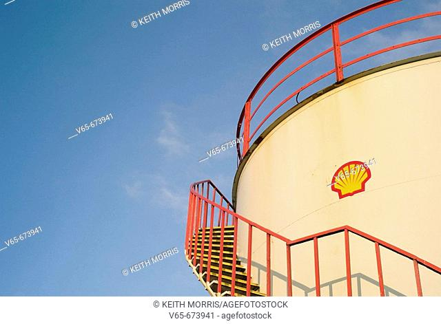 Shell Oil strorage tank, with company logo, Red metal walkway, against a clear blue sky. December 2007