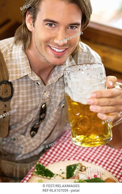 Young man drinking beer at Oktoberfest, Munich, Germany