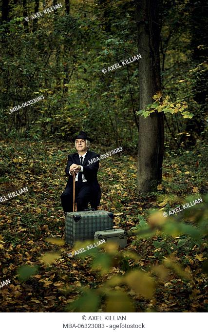 Man sitting in the forest with hat and stick and two suitcases