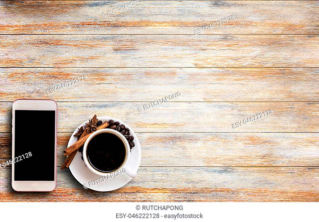 Top view cup of coffee and smart phone on old wooden table with copy space