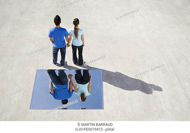 Rear view of man and woman holding hands with mirror on ground and reflection