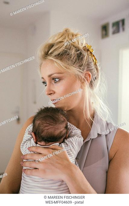 Mother holding her baby at home