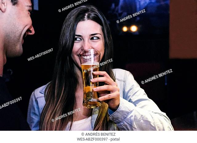 Smiling woman drinking a glass of beer with a man in a bar