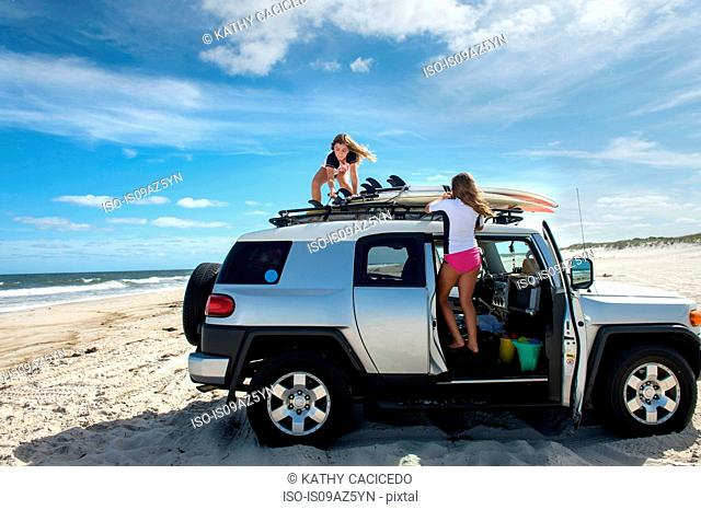 Two young girls untying surfboards from top of car