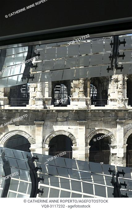 Vertical view of the Arena at Nimes through the reflective cladding of the Roman Museum, with their geometric forms mirroring the metal seating of the...
