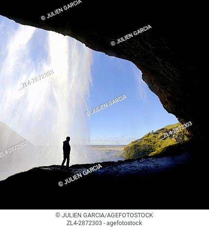 Iceland, Sudurland region, Seljalandsfoss waterfall, silhouette of man on a path passing behind the waterfall