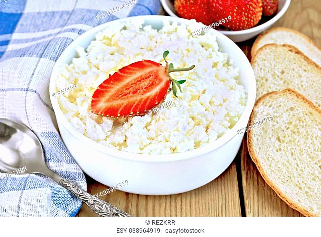 Cottage cheese in a white bowl with strawberries, a spoon, napkin, bread on a wooden boards background
