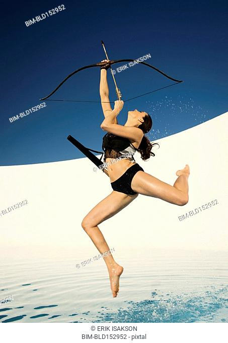 Caucasian woman aiming bow and arrow
