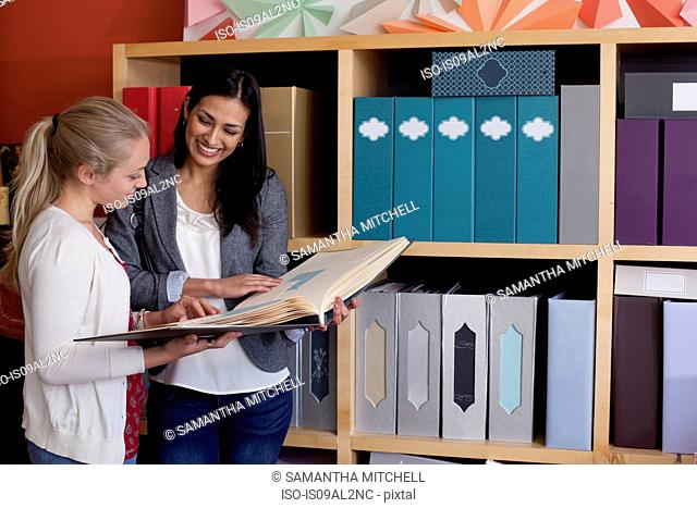 Customer and sales assistant browsing samples in stationery shop