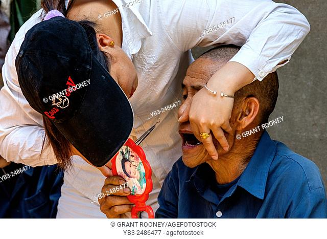 A Street Dentist Examines The Teeth Of An Elderly Man, Xingping Town near Guilin, Guangxi Province, China