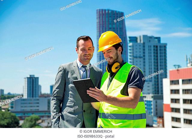 Businessman and construction worker, outdoors, looking at digital tablet