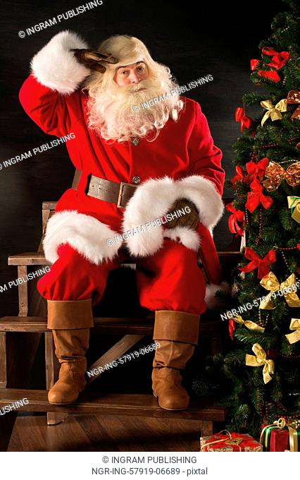 Authentic Santa Claus sitting near Christmas tree and looking tired after delivering all gifts to children