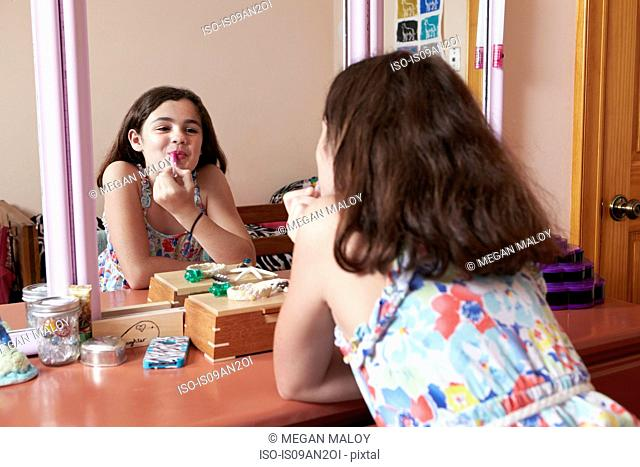 Girl applying lipstick in bedroom mirror