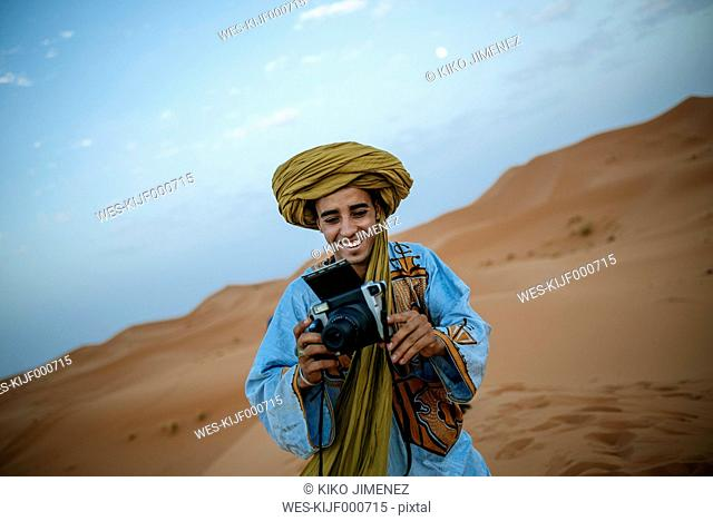 Young Berber taking pictures with camera
