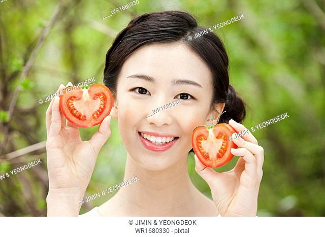 a woman holding a halved tomato in the nature