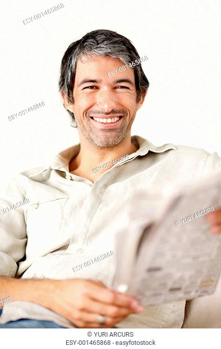 Portrait of handsome middle aged man smiling while reading newspaper